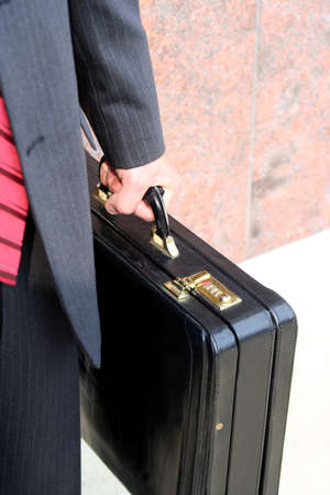Hand holding briefcase showing suit photo