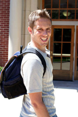 Male student with backpack walking into building Stock Photo - 547950