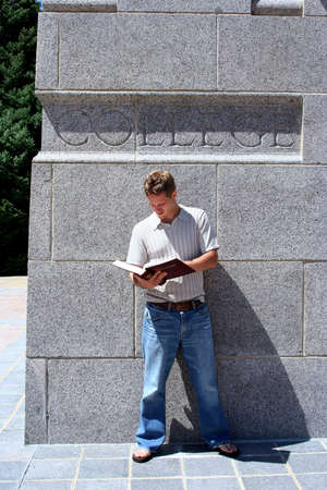 Male student reading against wall Stock Photo - 547951