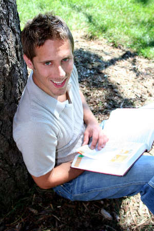 Student reading book against tree Stock Photo - 547831