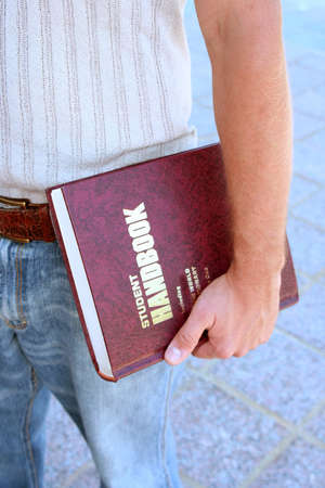 coed: Closeup of student handbook in hand