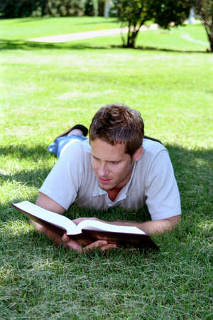 coed:  Student laying in grass reading book Stock Photo