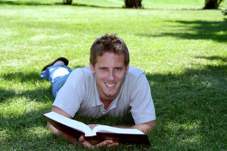 Student with book laying in grass Stock Photo - 547825