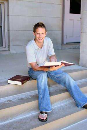 coed:  Male student reading student handbook