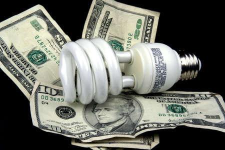 Energy saving light bulb on a pile of money