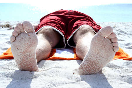 and the horizontal man: Closeup of bottom of feet on beach with sand sticking to them