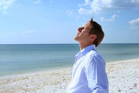 exuberance: Man lifting his face to sun on beach Stock Photo