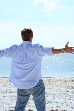 Man lifting his arms out to sides looking at ocean Stock Photo - 561482