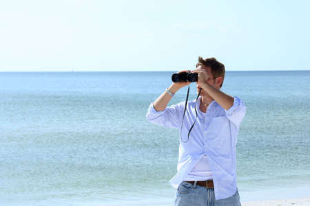 lies forward: Man on beach looking through binoculars