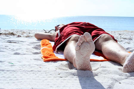 Man laying on beach shot from below feet