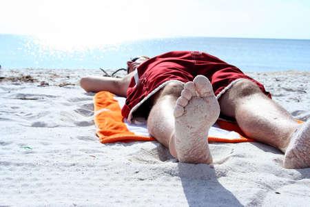 beach towel: Man laying on beach shot from below feet