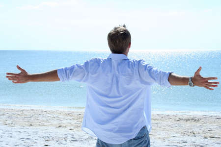 the sides: Man lifting his arms out to sides looking at ocean