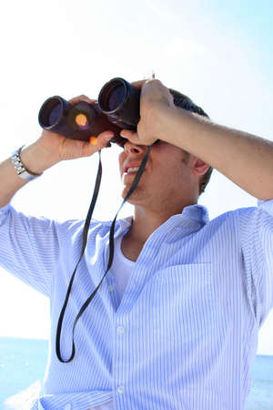untruth: Man on beach looking through binoculars with sun spots Stock Photo