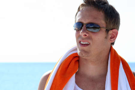 Headshot of man in sunglasses at beach with towel around shoulders photo