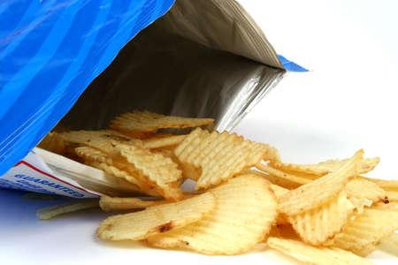 Potato chips spilling from bag Stock Photo