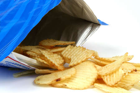 snacks: Potato chips spilling from bag Stock Photo