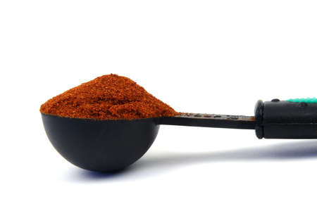 Red spice in a measuring spoon
