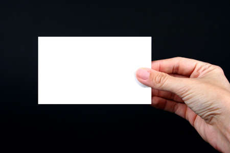 Hand holding a blank white card on a black background