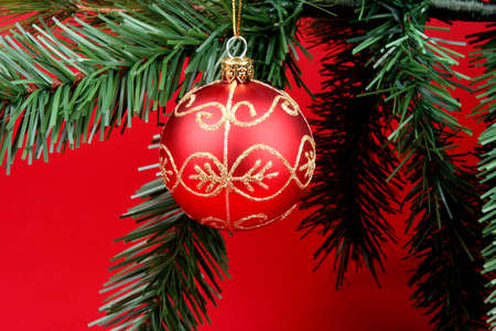 Christmas tree branch on a red background with red ball hanging from it Banco de Imagens