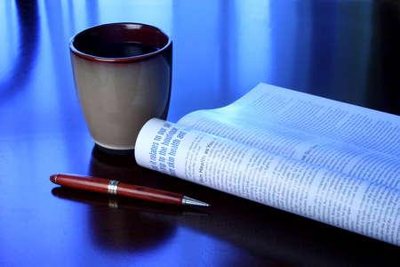 커피 잔, 잡지 및 블루 톤의 나무 책상에 펜
