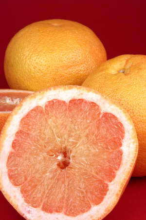Sliced grapefruit on a red background Stock Photo