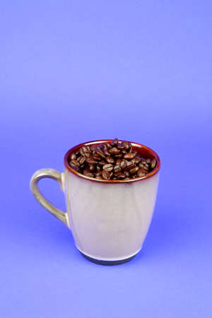 caffiene: Brown coffee mug filled with coffee beans on a blue background