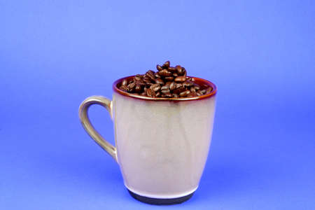 Brown coffee mug filled with coffee beans on a blue background