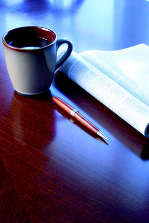 Coffee mug, magazine and pen on wood desk with blue tone Stock Photo - 614964