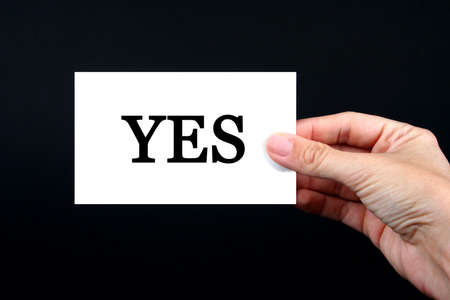 Hand holding a white card on a black background with the word yes on it