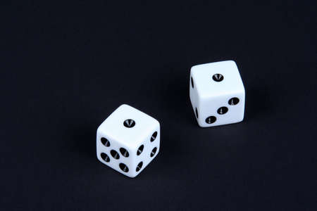 Two dice on a black background each rolled to a one