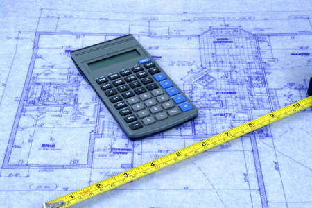 Calculator and tape measure on a blueprint of house photo