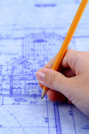 tabulation: Hand holding pencil to a blue print of house Stock Photo