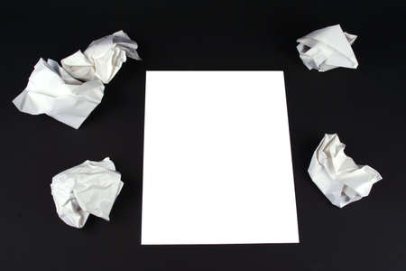 Piece of white paper on a black background with wads of crumpled paper around it Stock Photo - 656651