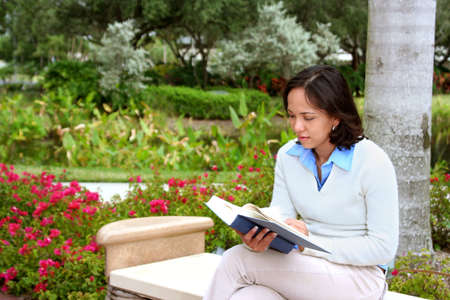 Young female student sitting on a bench with a book Stock Photo - 677958