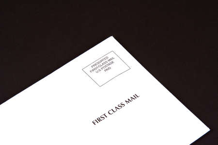 Corner of envelope of first class mail on a black envelope