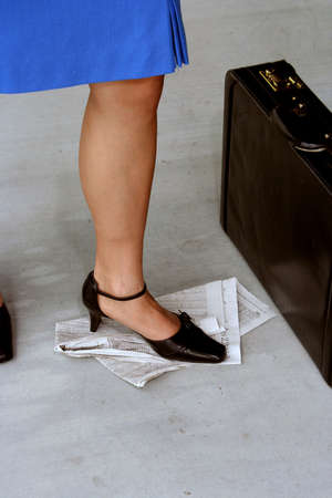 Womans foot stomping on stock pages from the newspaper