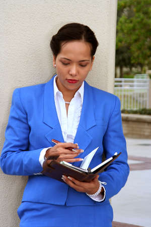 Businesswoman with a planner standing against a wall Stock Photo - 685979