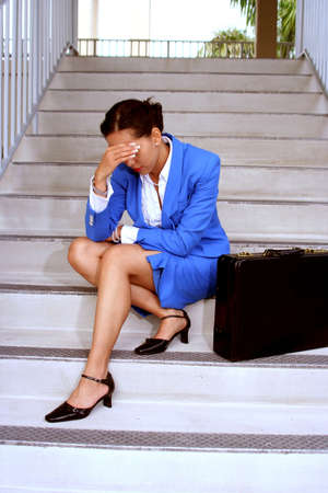 Businesswoman sitting on stairs looking stressed out
