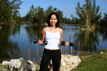 Woman at a park doing bicep curls with weights