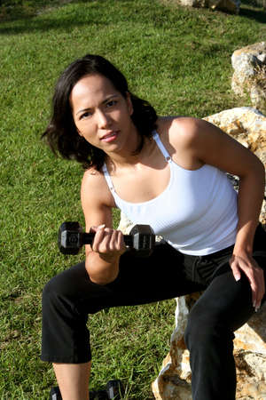 Woman at a park doing bicep curls with weights on rock photo