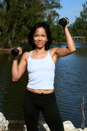 Woman at a park doing overhead presses with weights photo