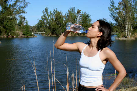 Woman drinking water outside after a workout