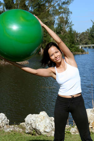 Woman doing side bends with a balance ball Imagens