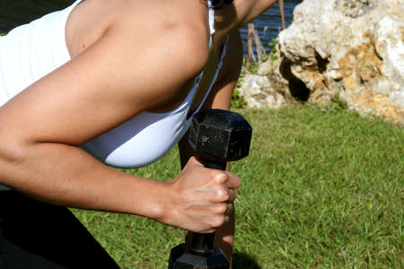 Woman at a park doing triceps kickbacks with weights photo