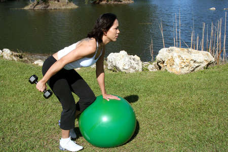 Woman at a park doing triceps kickbacks on a balance ball with weights photo