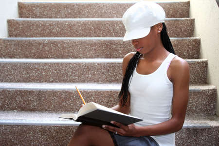 Young female student sitting and  reading  a book