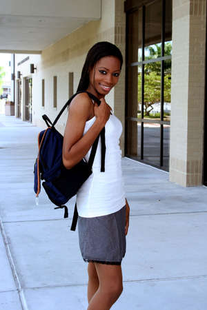 Female student walking on campus with a backpack Stock Photo