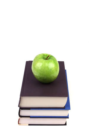 Three books in a stack with a green apple on top on a white background photo