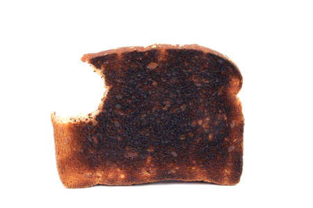 burnt toast: Piece of burnt toast with a bite on a white background Stock Photo