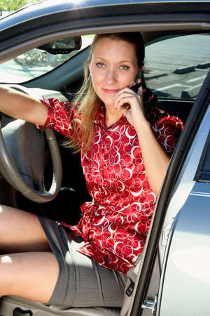 Businesswoman getting out of car while talking on cell phone